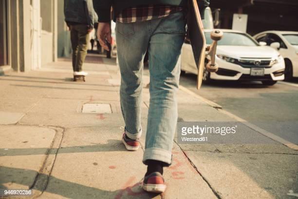 low section of man walking on sidewalk with skateboard - eislauf oder rollschuhlauf stock-fotos und bilder