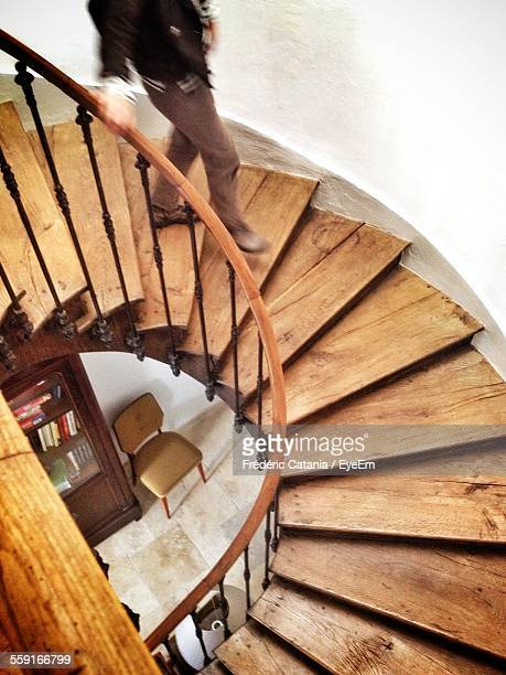 Low Section Of Man Walking On Spiral Staircase