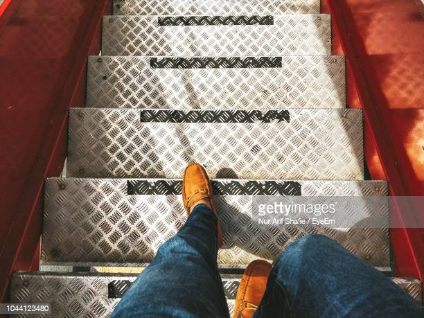 low section of man walking on staircase - low section stock pictures, royalty-free photos & images