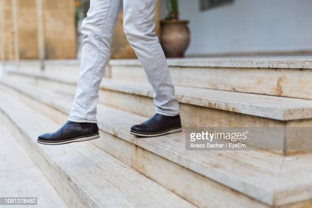 Low Section Of Man Walking On Staircase