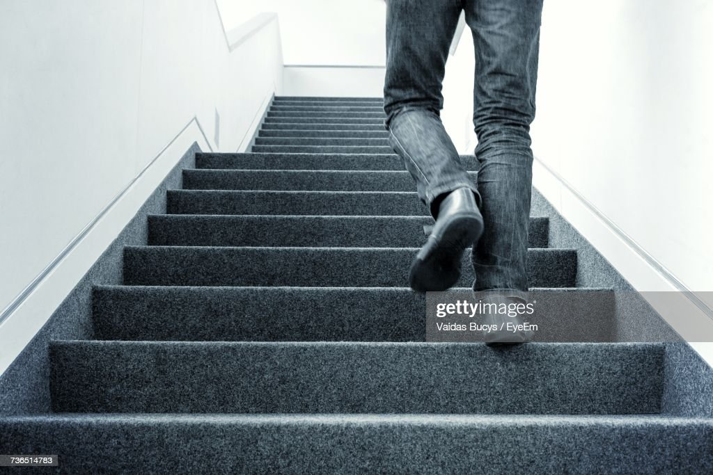 Low Section Of Man Walking On Stairs : Stock Photo