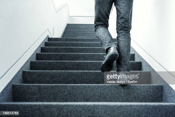 low section of man walking on stairs - stairs stock photos and pictures