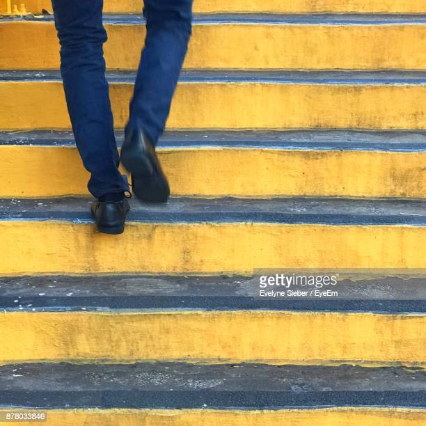 low section of man walking on steps - steps stock photos and pictures