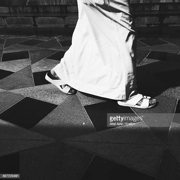 low section of man walking on tiled floor - sandal stock pictures, royalty-free photos & images