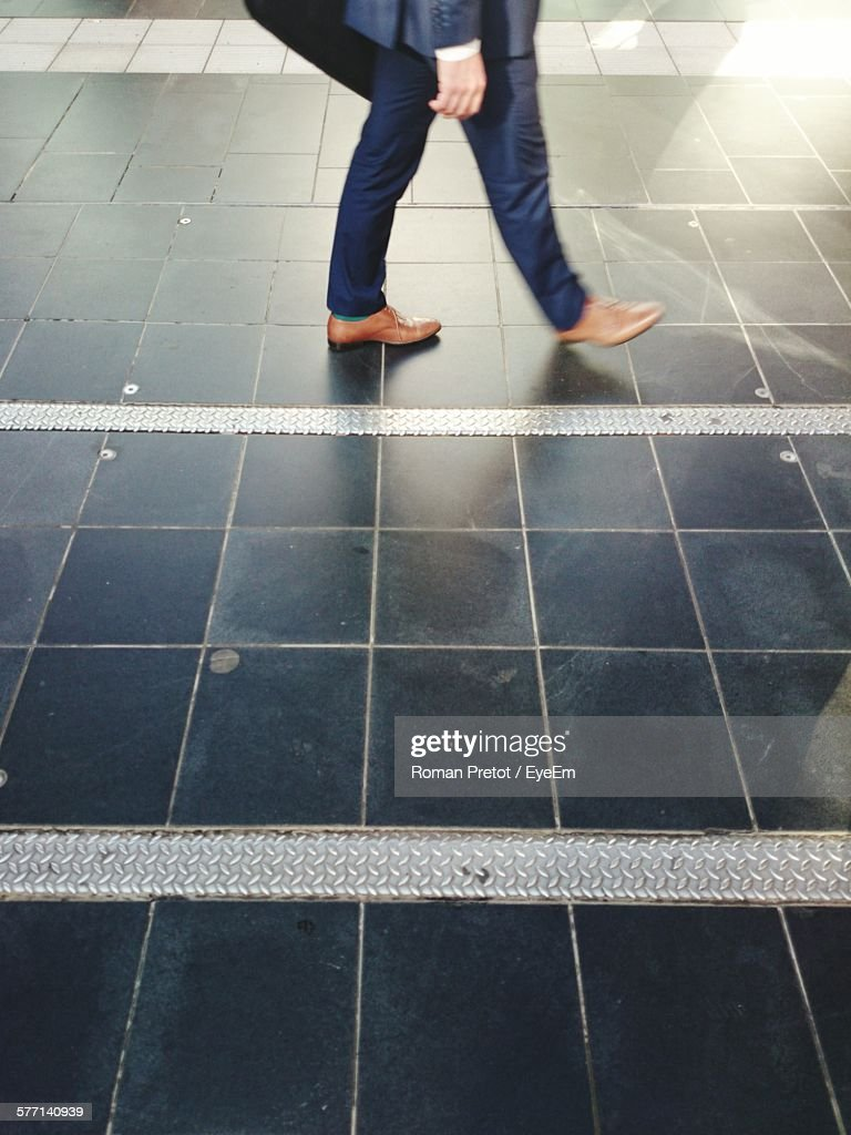 Low Section Of Man Walking On Tiled Floor : Stock-Foto