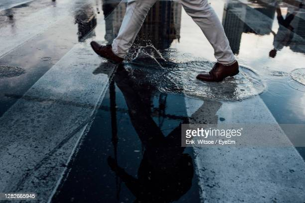 low section of man walking on wet street - poland stock pictures, royalty-free photos & images