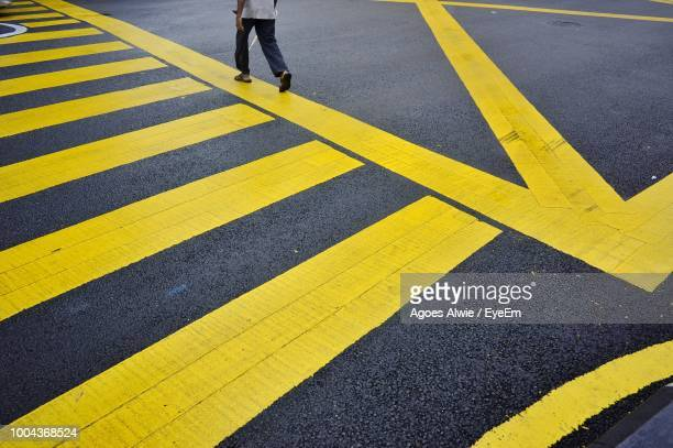 low section of man walking on zebra crossing - zebra crossing stock photos and pictures