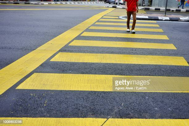 low section of man walking on zebra crossing - zebra crossing stock pictures, royalty-free photos & images
