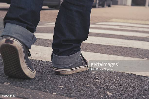 low section of man walking on zebra crossing - pedestrian crossing stock photos and pictures
