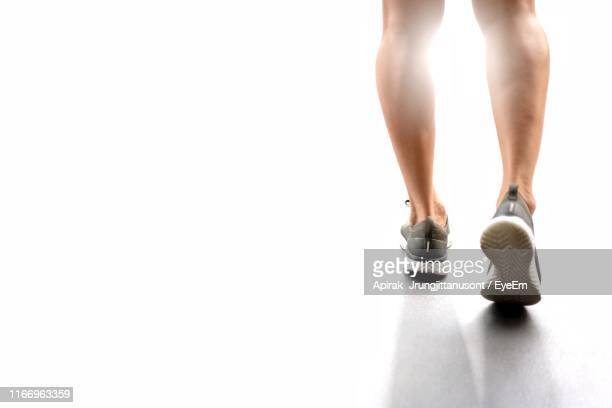 low section of man walking over white background - white shoe stock pictures, royalty-free photos & images