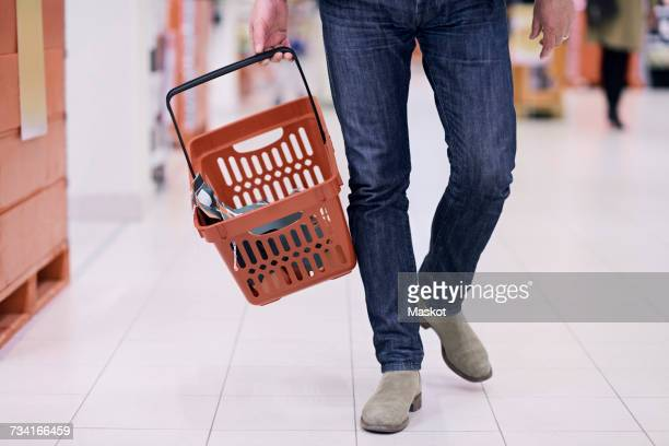 Low section of man walking with basket in supermarket