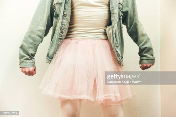 low section of man wearing a skirt standing against white background - transgender foto e immagini stock