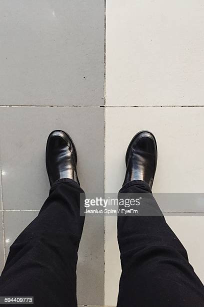 Low Section Of Man Wearing Black Shoes On Tiled Floor