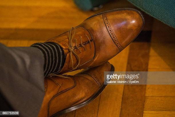 Low Section Of Man Wearing Brown Shoes On Floorboard