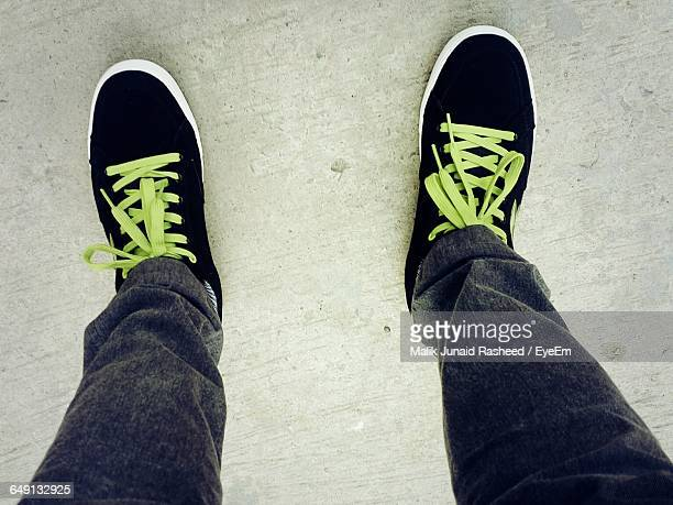 Low Section Of Man Wearing Canvas Shoes Standing On Floor
