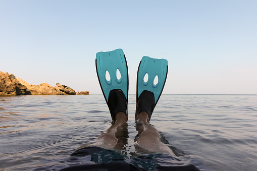 Low Section Of Man Wearing Diving Flippers In Sea Against Clear Sky - gettyimageskorea
