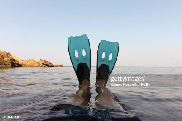 low section of man wearing diving flippers in sea against clear sky - personal perspective stock pictures, royalty-free photos & images