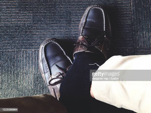 low section of man wearing dress shoes on floor - mens dress shoes stock pictures, royalty-free photos & images
