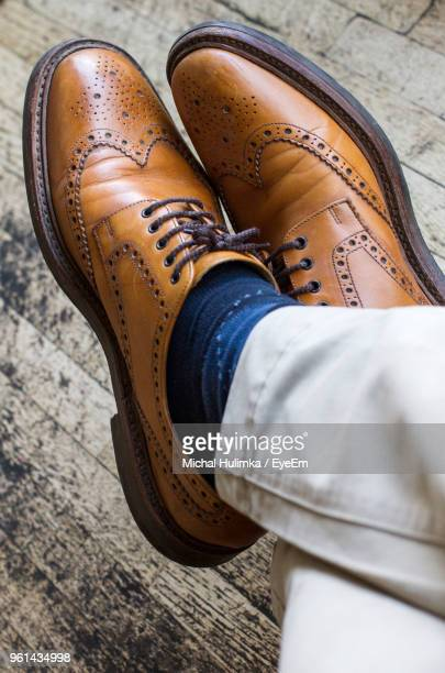 low section of man wearing dress shoes on wooden floor - dress shoe stock pictures, royalty-free photos & images