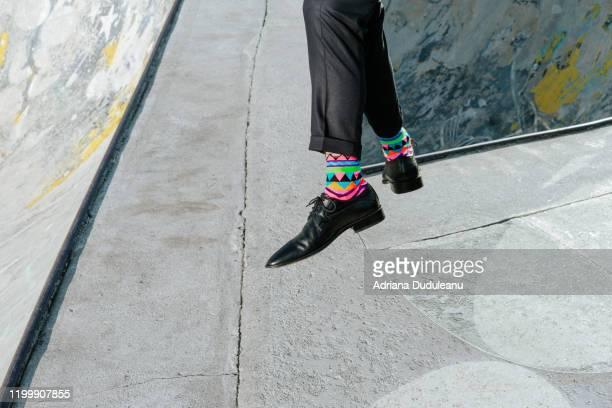 low section of man wearing forma shoes skateboarding on footpath - formal imagens e fotografias de stock