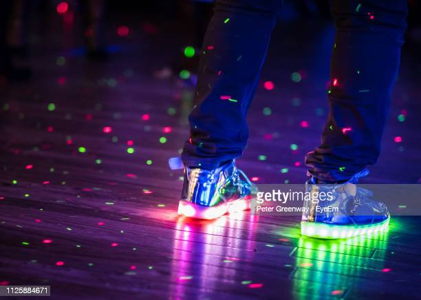 low section of man wearing illuminated shoes on dance floor - ディスコ照明 ストックフォトと画像