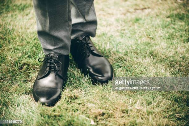 low section of man wearing leather shoes while standing on grass - leather shoe stock pictures, royalty-free photos & images