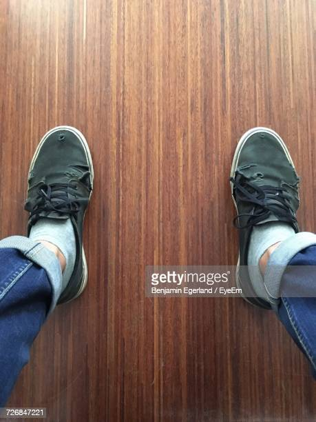 Low Section Of Man Wearing Old Shoes On Hardwood Floor