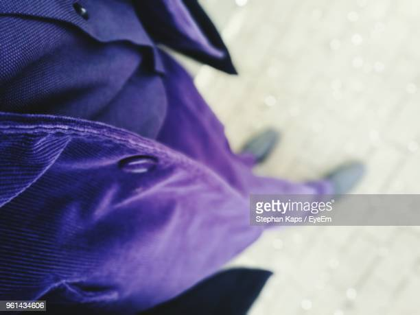 low section of man wearing purple suit on footpath - purple suit stock pictures, royalty-free photos & images