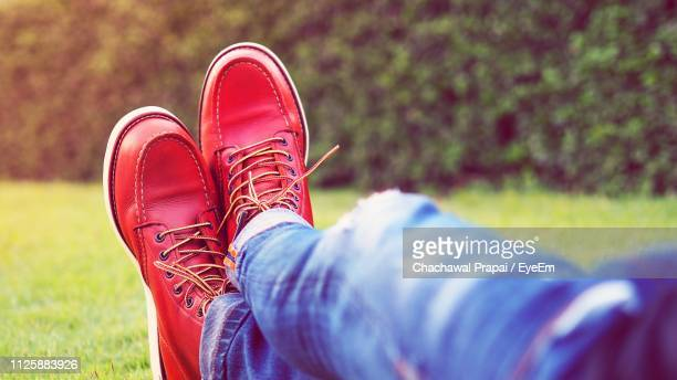 low section of man wearing red shoes on grassy field - red shoe stock pictures, royalty-free photos & images