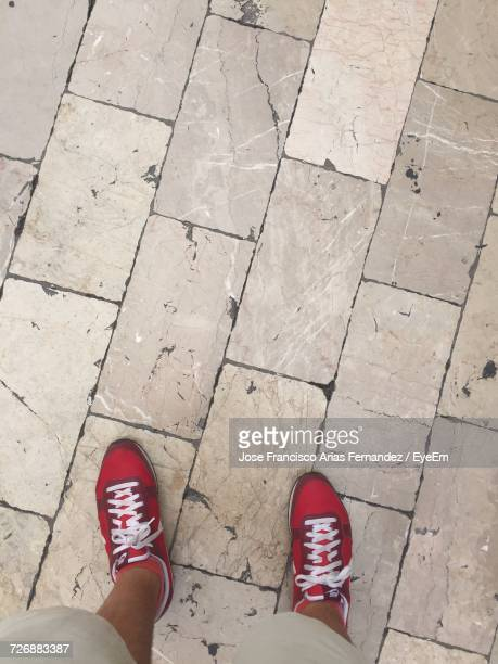 Low Section Of Man Wearing Red Shoes Standing On Paving Street