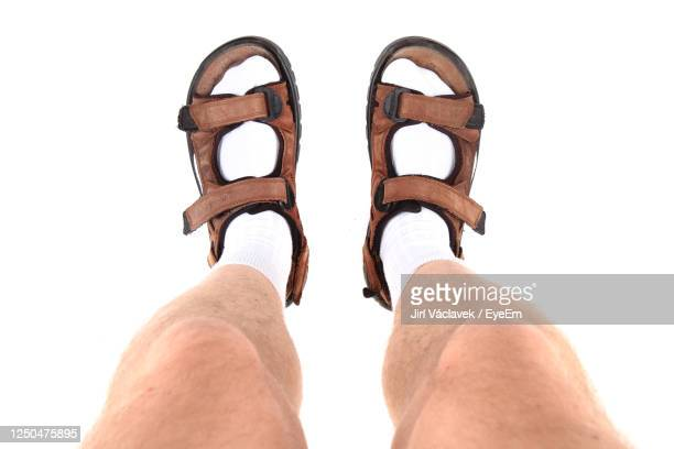low section of man wearing sandals against white background - open toe stock pictures, royalty-free photos & images