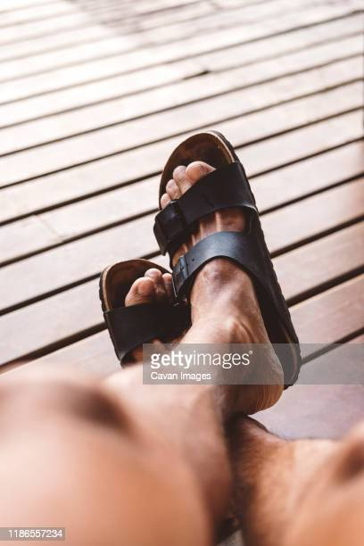 low section of man wearing sandals on hardwood floor at home - open toe stock pictures, royalty-free photos & images