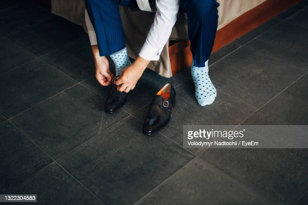 low section of man wearing shoes at home - lino stock pictures, royalty-free photos & images