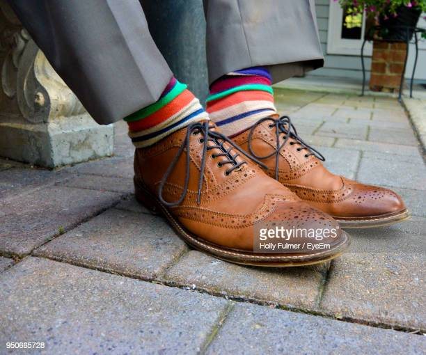 low section of man wearing shoes on footpath - dress shoe stock pictures, royalty-free photos & images