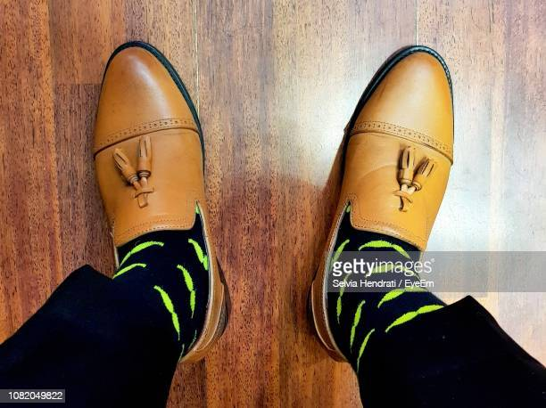 low section of man wearing shoes on hardwood floor - brown shoe stock photos and pictures