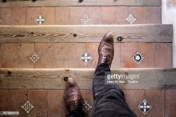 Low Section Of Man Wearing Shoes On Steps