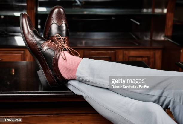 low section of man wearing shoes - feet up stock pictures, royalty-free photos & images