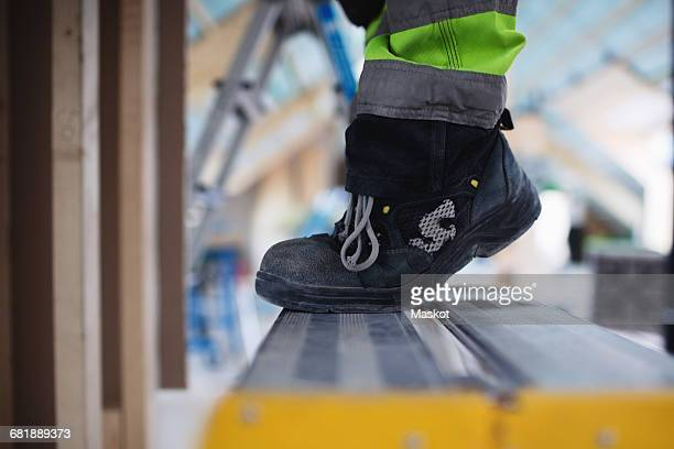 low section of man wearing shoes standing on ladder - work shoe stock photos and pictures