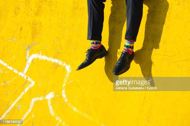 low section of man wearing shoes while sitting on yellow wall - yellow shoe stock pictures, royalty-free photos & images