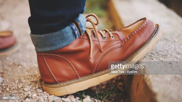 Low Section Of Man Wearing Shoes While Standing On Footpath