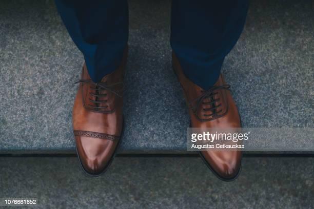 low section of man wearing shoes while standing on steps - leren schoen stockfoto's en -beelden