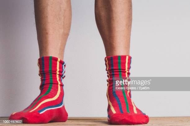 low section of man wearing socks while standing against white background - men in white socks fotografías e imágenes de stock