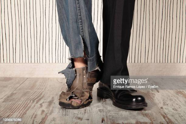 low section of man wearing torn jeans and pants while standing on floor - named animal ストックフォトと画像