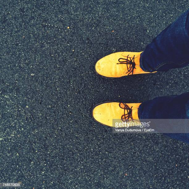 low section of man wearing yellow shoes while standing on wet road - sapato preto - fotografias e filmes do acervo