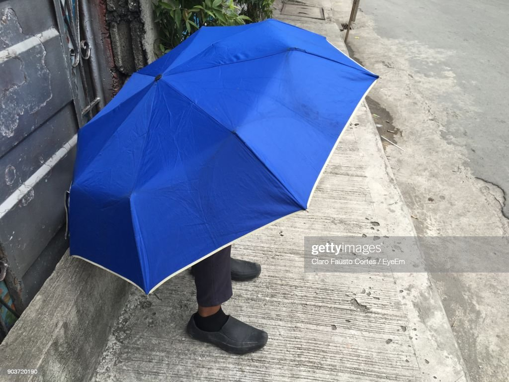 Low Section Of Man With Blue Umbrella On Sidewalk Stock Photo