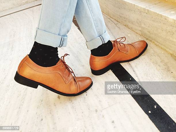 low section of man with brown leather shoes - brown shoe stock photos and pictures