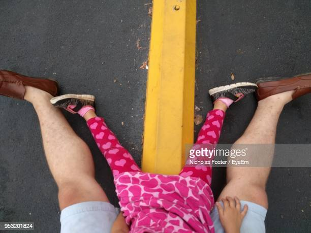 low section of man with daughter sitting at road - low section stock pictures, royalty-free photos & images