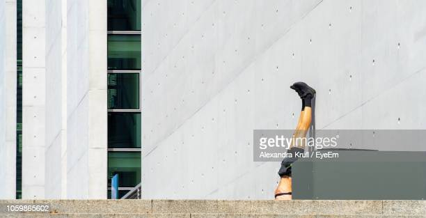 Low Section Of Man With Feet Up On Wall