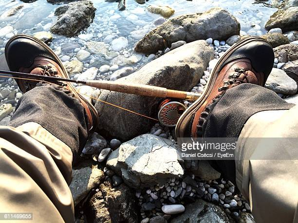 Low Section Of Man With Fishing Rod Relaxing At Rocky Riverbank