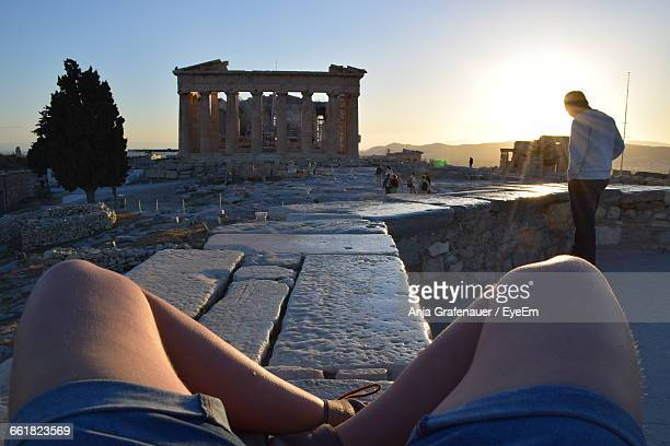 Low Section Of Man With Friend Visiting Parthenon Against Clear Sky During Sunset
